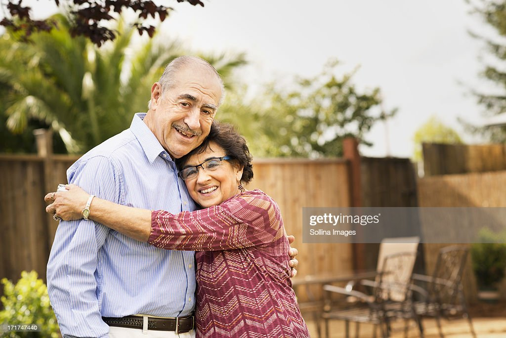 Elderly couple smiling and hugging