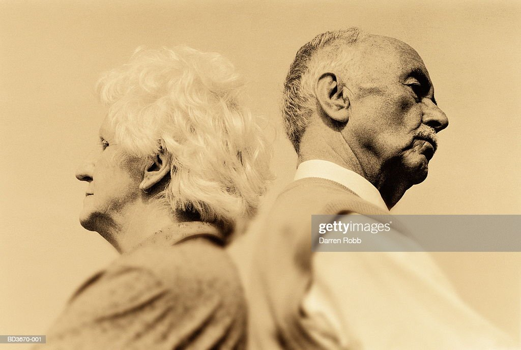 Elderly couple standing back to back (sepia tone) : Stock Photo