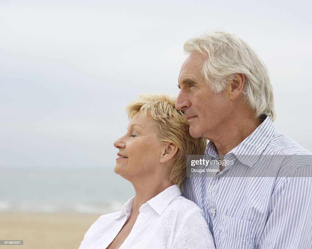 Elderly couple standing together at beach. : Stock Photo