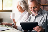 Daily life. Old grey man in glasses using laptop while woman drinking tea and smiling