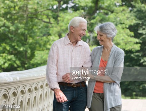 Elderly couple walking in the park smiling