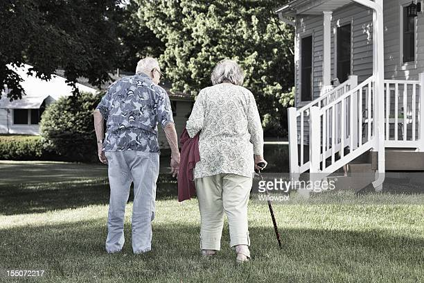 Elderly Couple Walking Together in Back Yard