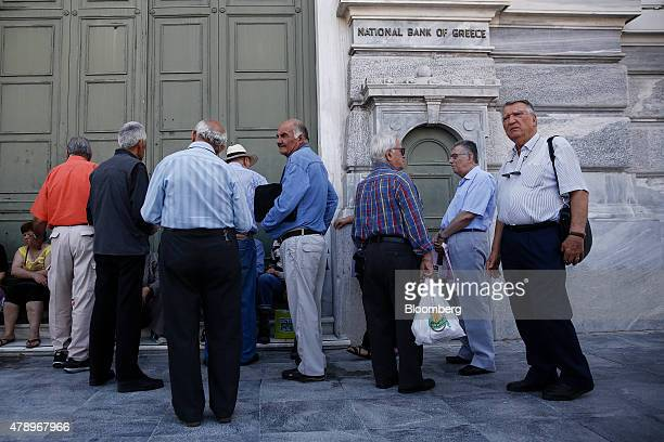 Elderly customers wait outside the headquarters of the National Bank of Greece SA in the hope that it might open in Athens Greece on Monday June 29...