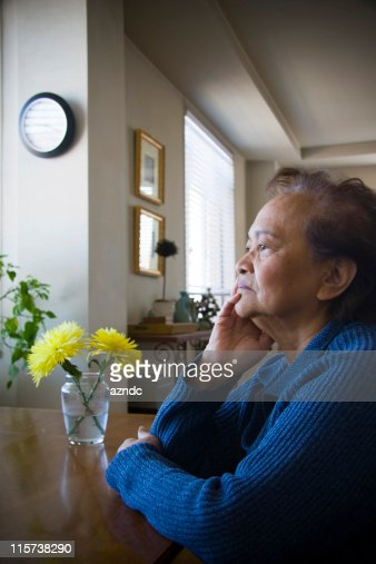 Elderly female sitting in solitude in a room
