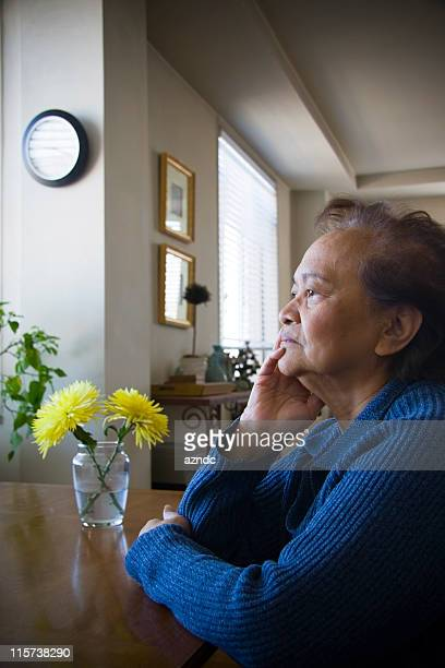 Elderly female sitting in solitude in a room