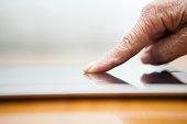 Elderly finger pointing on digital tablet