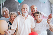 Smiling elderly man and his friends with balloons enjoying birthday party