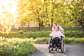 Elderly grandmother in wheelchair with an adult granddaughter outside in spring nature.