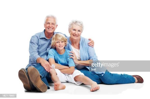 Elderly grandparents with grandson on white floor
