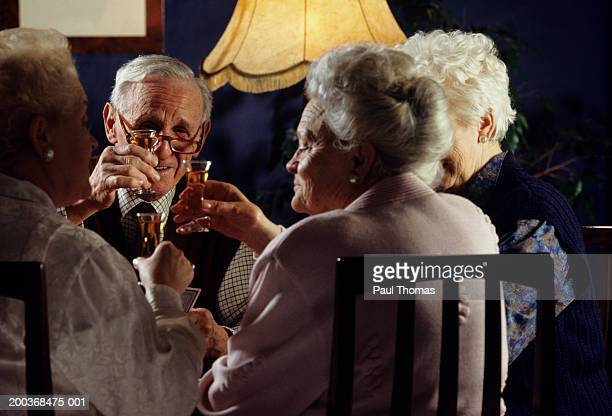 Elderly group playing cards, drinking sherry