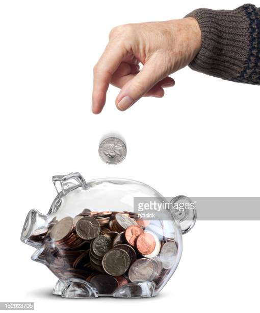 Elderly Hand Dropping Coin Into Clear Nearly Full Piggy Bank