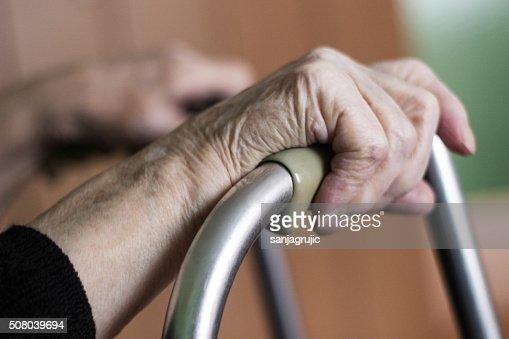 Elderly hands on a walker : Stock Photo