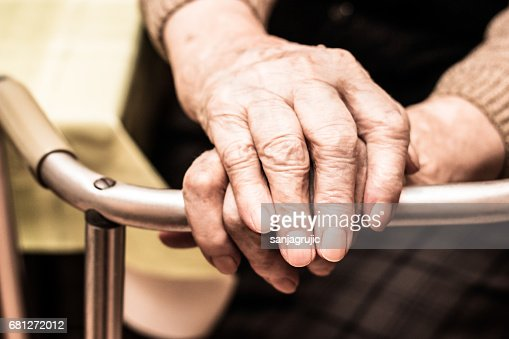 Elderly hands on a walker : Stock Photo