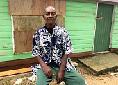 Elderly indigenous Fijian man in her 70's sit outside his village home. Real people copy space