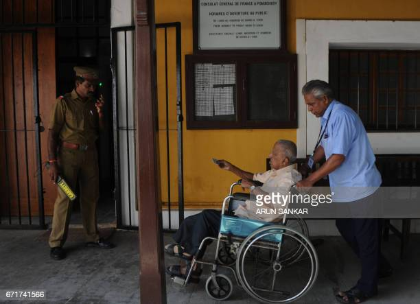 A elderly IndoFrench citizen is transported by wheelchair by an assistant on the premises of a polling booth in Puducherry on April 23 before casting...