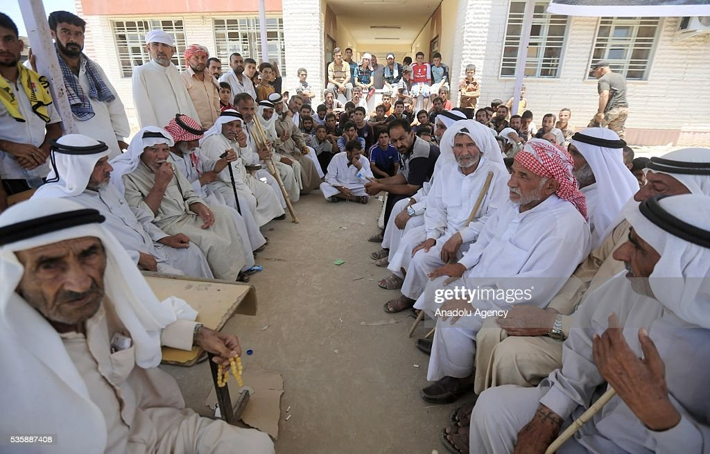 Elderly Iraqi people sit on the benches as they leave their home in Fallujah town due to conflicts between Daesh and security forces in Anbar, Iraq on May 30, 2016. Some of the families who left their home are placed in a school in Karma Town, west of Anbar city.