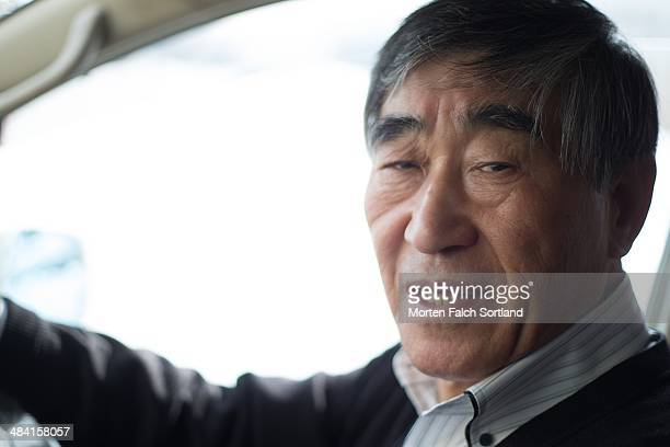 Elderly Japanese man driving a car picture showing his head and upper body