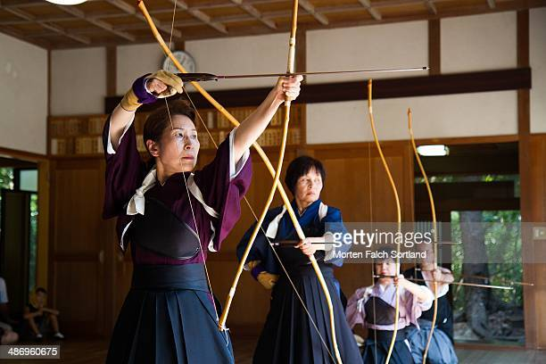 Elderly Japanese women preparing their Kyudo bows for shooting