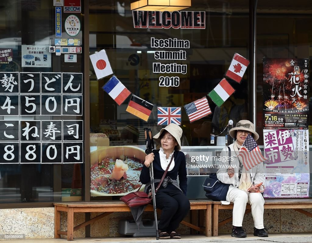 Elderly Japanese women sit under a welcome message outside a shop during the world leaders' visit to the Ise-Jingu Shrine in the city of Ise, Mie prefecture on May 26, 2016 on the first day of the G7 leaders summit. World leaders kicked off two days of G7 talks in Japan on May 26 with the creaky global economy, terrorism, refugees, China's controversial maritime claims, and a possible Brexit headlining their packed agenda. / AFP / Foreign Ministry of Japan / MANAN