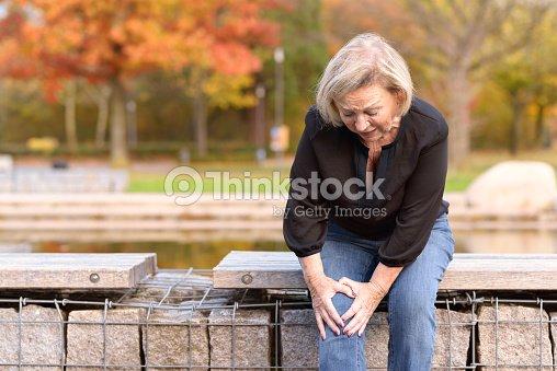 Elderly lady grabbing her knee in pain : Stock Photo