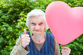 Picture of a cute elderly lady celebrating birthday with a heart shaped balloon in the park, outdoor