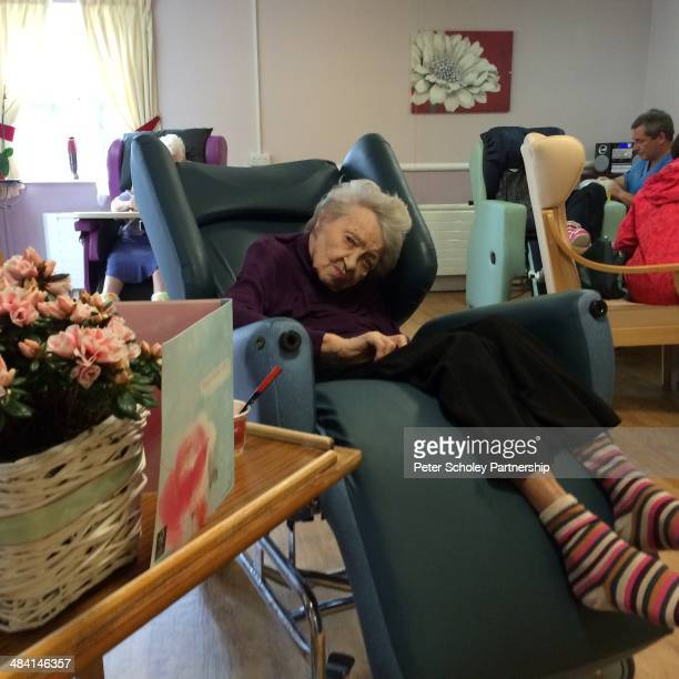 Elderly lady on reclining chair in nursing home lounge