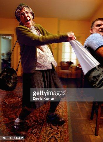 Elderly Lady Pulls Man's Pants : Stock Photo