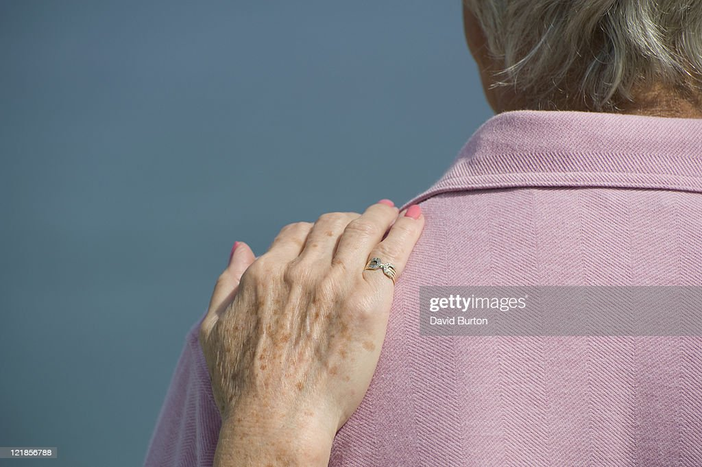 Elderly lady resting her hand on her partners shoulder : Stock Photo