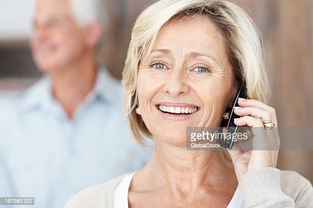 Idosos senhora a falar no cellphone com Homem no fundo