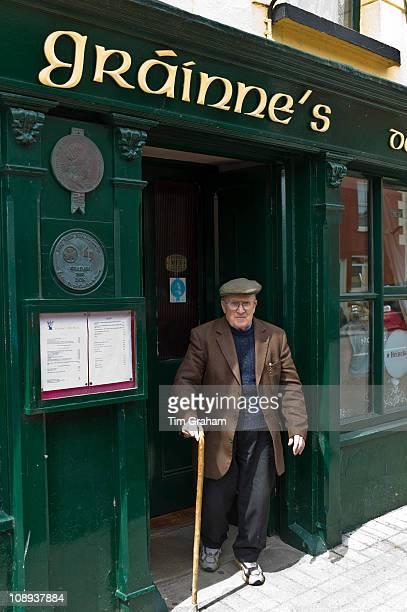 Elderly local Irishman with walking stick leaving Grainne's Bar in Mill Street Timoleague West Cork Ireland