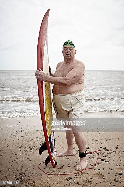 Elderly male surfer holding his surf board
