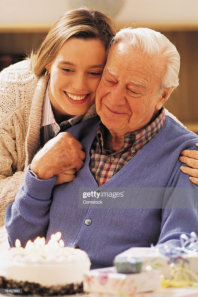 Elderly man and adult daughter with birthday cake : Stock Photo