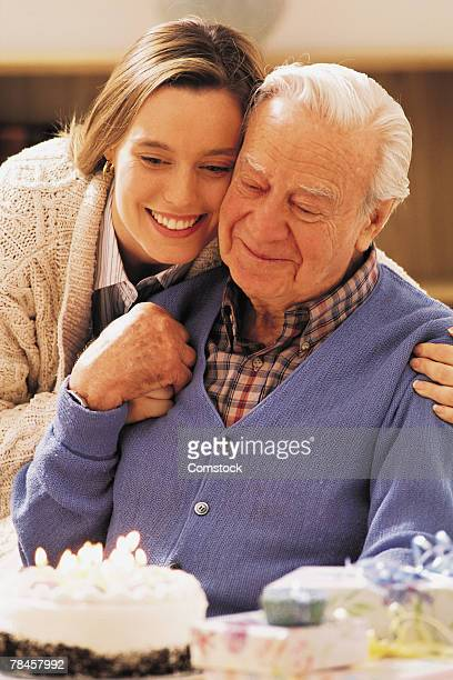 Elderly man and adult daughter with birthday cake
