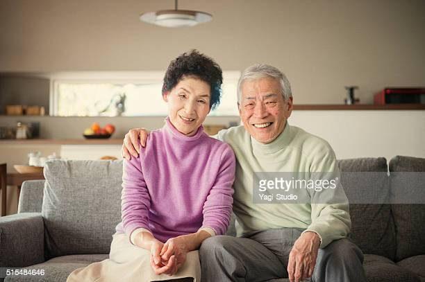 年配の男性と女性のソファに座る