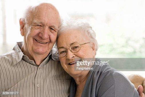 Anciano y mujer sentada en un sofá cama
