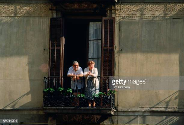 Elderly man and woman watching from the balcony of their home in SevilleSpain