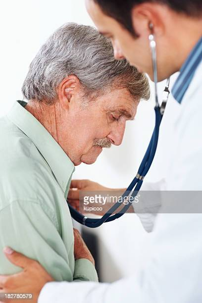 Elderly man being examined with a stethoscope