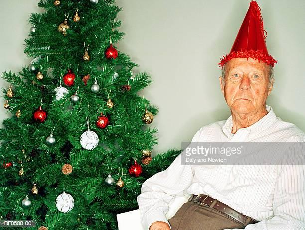 Elderly man beside Christmas tree, portrait