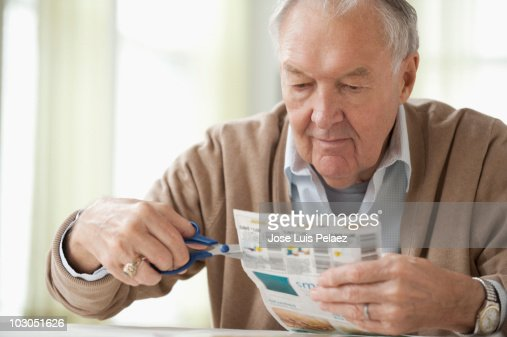 Elderly man clipping out coupons