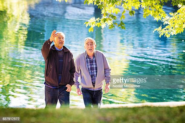 Elderly man discusses trees with male friend in park