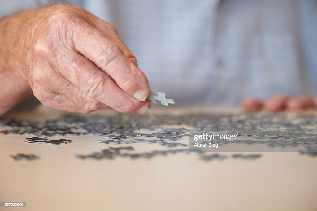 Elderly man doing jigsaw puzzle