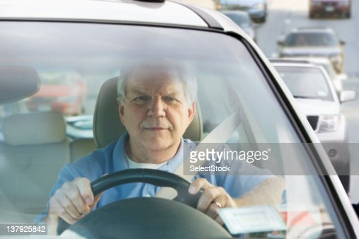 Elderly man driving car in traffic : Stock Photo