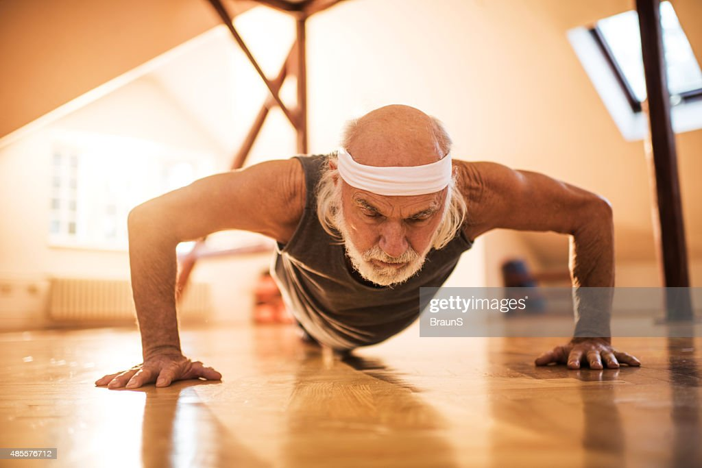 Elderly man exercising push-ups in a health club.