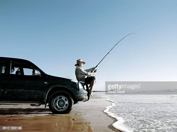 Elderly Man Fishing in Ocean