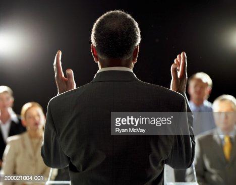Elderly man giving speech at podium, rear view : Stockfoto