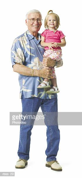 Elderly man in a blue shirt smiles as he holds his young granddaughter.