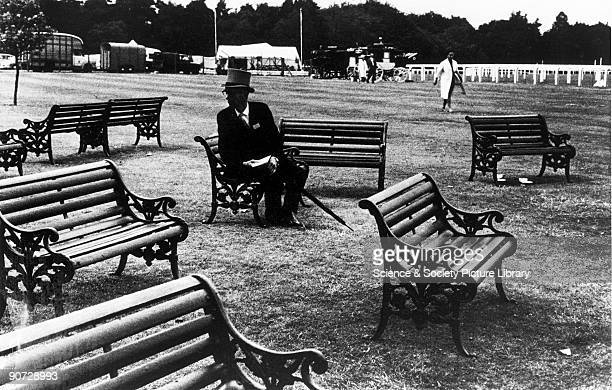Elderly man in a top hat sitting alone amongst public benches at Ascot horse races Berkshire Photographer Tony RayJones created most of his images of...