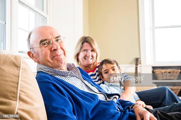 Homem idoso com camisola azul com a família no sofá