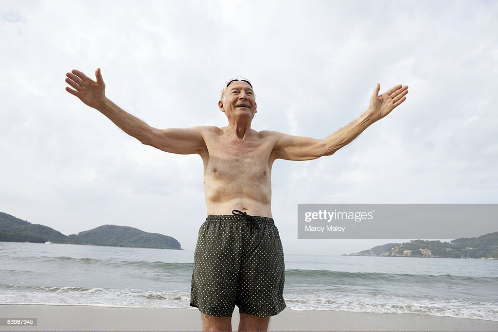 Elderly Man In Swim Trunks On Beach With Arms Out Stock