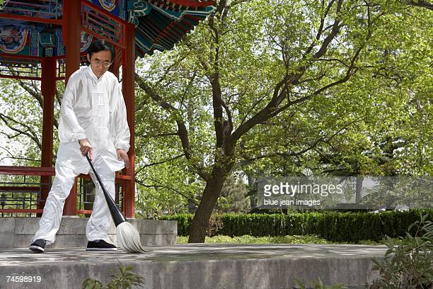 Elderly man in traditional Chinese clothes draws characters on the ground.
